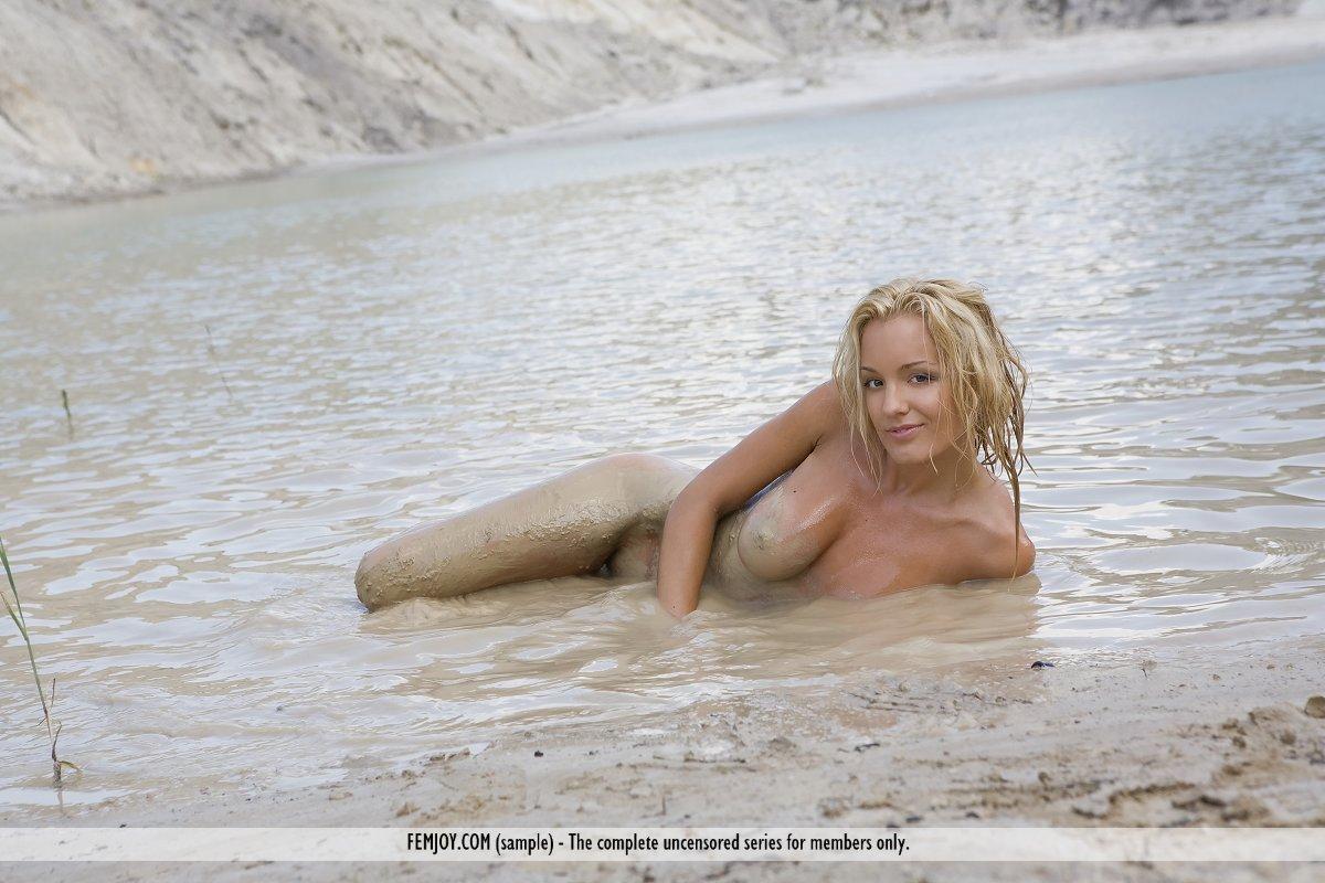 Голая модель со свелыми волосами Nati Femjoy и режиссер делают обнаженную фотосессию на берегу моря
